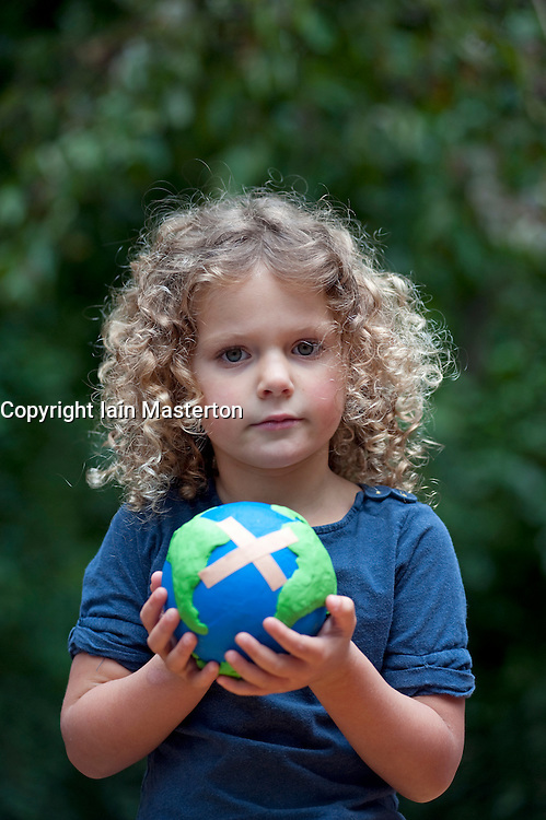 young girl holding a model of a sick planet Earth with a Band-aid stuck to it