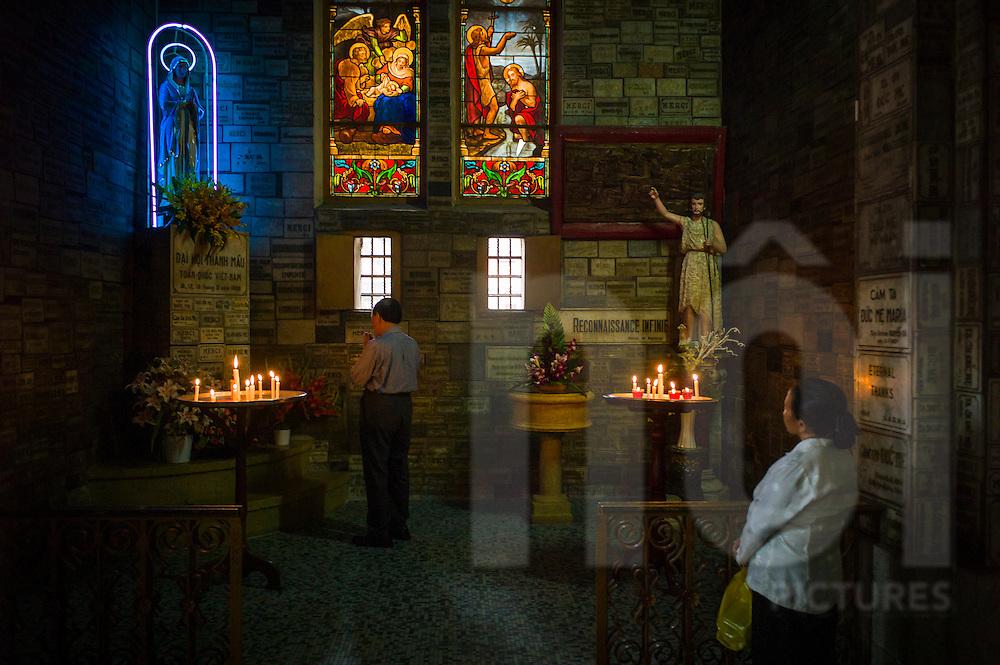 A vietnamese man is praying in Saigon Notre Dame Basilica, HCMC, Vietnam, Southeast Asia