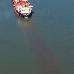 Aerial Photograph of the Narova Tanker Ship petroleum vessel  along Delaware River near  Philadelphia, Pa. Notice oil excess or disbursing from under ship.