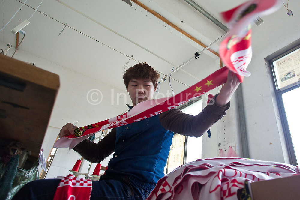 A worker sorts football scarves at  the Yiwu Wells Knitting Products Co., Ltd factory in Yiwu, Zhejiang Province, China on 06 March  2013.<br /> The city of Yiwu is known as one of China's largest trading centers for small merchandise and light industry, drawing buyers from around the world. Uncertain global demand, a stronger yuan currency and rising labour costs have taken their toll on Chinese exporters, but analysts believe sales could pick up modestly in 2014 due to improved demand from the United States and Europe.