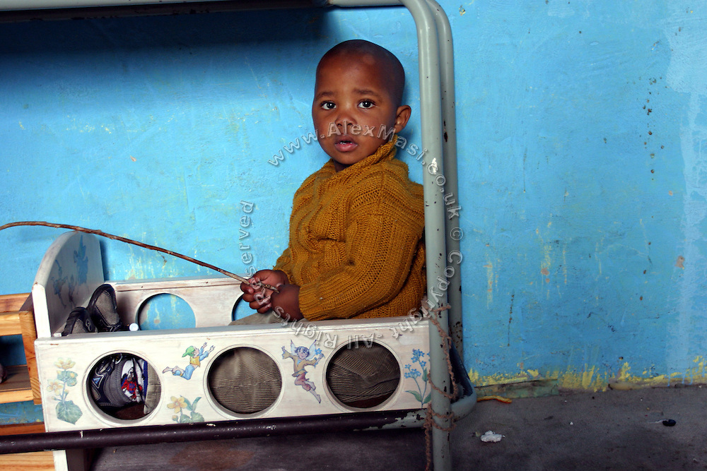 A child is sitting at a creche in Khayelitsha township in Cape Town, where over a million people live in the extreme poverty..