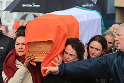 © London News Pictures. 21/03/2017. Derry, UK. Bernadette Canning (right) carrys the coffin of her husband Martin McGuinness in the Bogside area of Derry, Northern Ireland, 21 March 2017. Sinn Féin's Martin McGuinness, Northern Ireland's former deputy first minister died aged 66 early this morning. It is understood he had been suffering from a rare heart condition. The former IRA leader turned peacemaker worked at the heart of the power-sharing government following the 1998 Good Friday Agreement. He became deputy first minister in 2007, standing alongside Democratic Unionist Party leaders Ian Paisley, Peter Robinson and Arlene Foster.. Photo credit: LNP