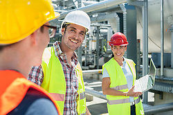Happy engineer with his colleagues in meeting with laptop at geothermal power station, Bavaria, Germany