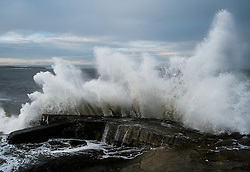 © Licensed to London News Pictures. 19/01/2014<br /> <br /> Teesside, England<br /> <br /> A wave crashes over the sea wall at South Gare at the mouth of the Tees in Cleveland.<br /> <br /> Photo credit : Ian Forsyth/LNP