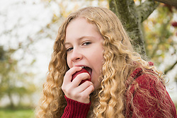 Portrait of a blond teenage girl biting into an apple in apple orchard, Bavaria, Germany
