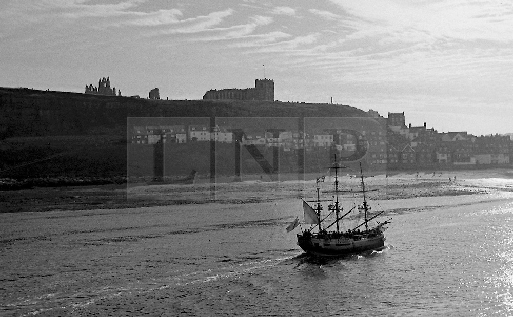 © Licensed to London News Pictures.01/11/15<br /> Whitby, UK. <br /> <br /> A tourist boat sails into the harbour during the Whitby Goth weekend in Whitby, North Yorkshire. The event began in 1994 to celebrate goth culture and music and takes place twice each year. <br /> Thousands of extravagantly dressed people attend the popular event wearing Steampunk, Cybergoth, Romanticism, Victoriana and other clothing as they take part in the celebration of Goth culture. <br /> <br /> Note to Editors - Picture shot on Kodak Tri X 400ISO film.<br /> Photo credit : Ian Forsyth/LNP