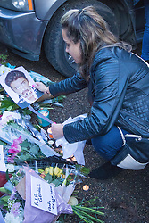 Highgate, London, December 26th 2016. Fans gather outside the London home of pop icon George Michael who died on Christmas day. PICTURED: A woman places a picture of George Michael amongst the tributes.
