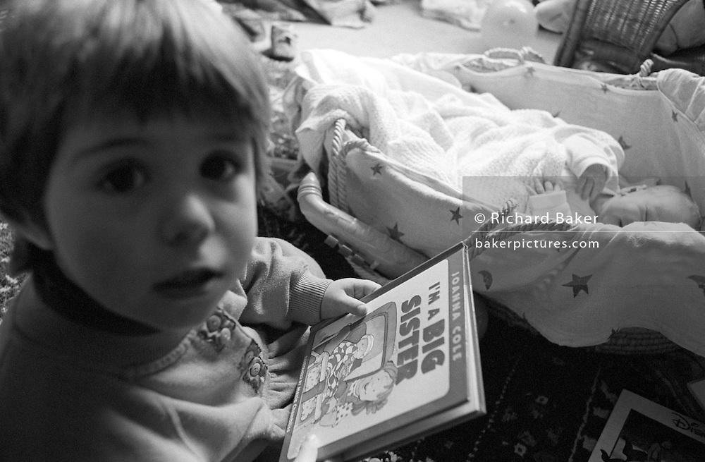 A 2 year-old girl reads a book about being a big sister, coming to terms with role-play, the idea of having a newborn baby brother in his basket at home in south London.