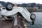 A car bent over a bridge by the  tsunami that struck the north east coast of Japan on March 11th. Kamaishi, Iwate, Japan. March 17th 2011