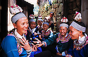 Smiling Miao woman and young girls in traditional costume, Duyun, Guizhou Province, China