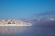 Small wooden huts on the banks of a lake in Jarfjord, near Kirkeness, Finnmark region, northern Norway