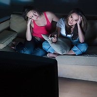pictures in a living room of two young girls sitting on a couch geting bored by watching tv
