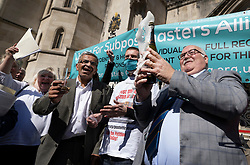 © Licensed to London News Pictures. 23/04/2021. London, UK. Tom Hedges holds up a bottle of Prosecco as he celebrates the verdict with other former Post Office sub-postmasters  outside The High Court. The Appeal Court has cleared the names of a group of 42 sub-postmasters - some of whom were jailed for stealing money after the Horizon accounting software was installed at Post Offices. At a previous High Court hearing a judge found the Fujitsu accounting system had major faults and defects. The Post Office has already agreed to pay £58m in a settlement with more than 500 sub-postmasters. <br /> Six convictions were overturned last year . Photo credit: Peter Macdiarmid/LNP
