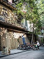 Bamboo poles stand against the facades of shops along Hang Vai street known for bamboo products in Hanoi's Old Quarter, Vietnam, Southeast Asia