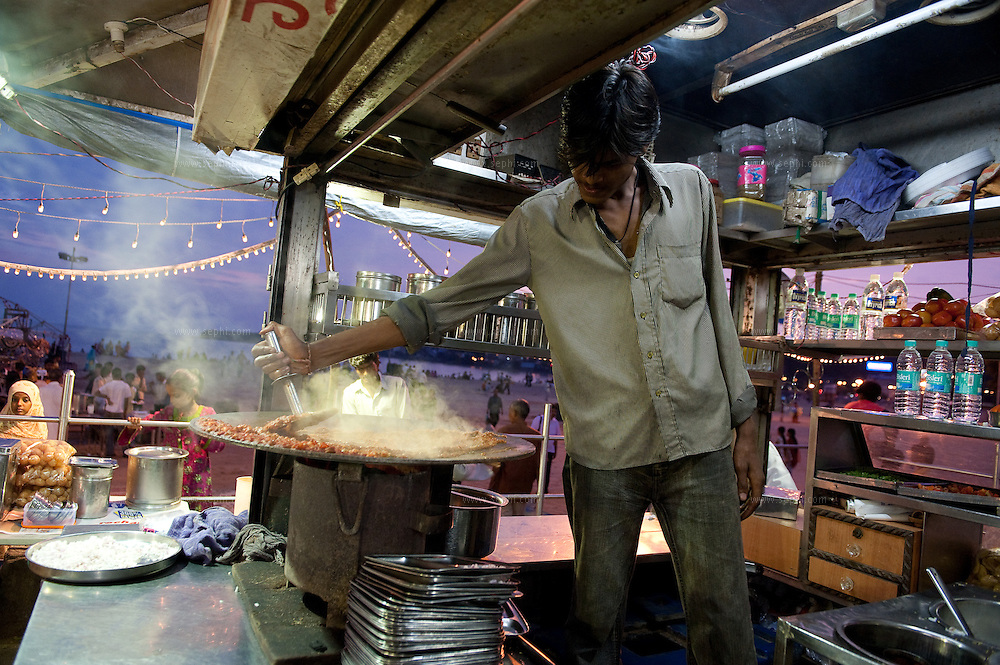 A vendor at a street food stall on Chowpati beach in Mumbai prepares Pao Bhaji, a favorite mumbai snack.