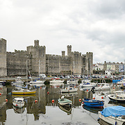A panorama of the castle in the background with boats moored on teh River Seiont in the foreground at Caernarfon Castle in northwest Wales. A castle originally stood on the site dating back to the late 11th century, but in the late 13th century King Edward I commissioned a new structure that stands to this day. It has distinctive towers and is one of the best preserved of the series of castles Edward I commissioned.