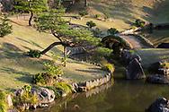 An arched stone bridge and pond in the Gyokusen'in maru Garden in Kanazawa, Ishikawa, Japan
