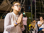 31 DECEMBER 2014 - BANGKOK, THAILAND:  A woman prays on New Year's Eve at Wat Pathum Wanaram in Bangkok. Hundreds of thousands of people pack into the Ratchaprasong Intersection in Bangkok for the city's annual New Year's Eve countdown. Many Thais go the Erawan Shrine and Wat Pathum Wanaram near the intersection to pray and make merit before going to their New Year's parties.   PHOTO BY JACK KURTZ