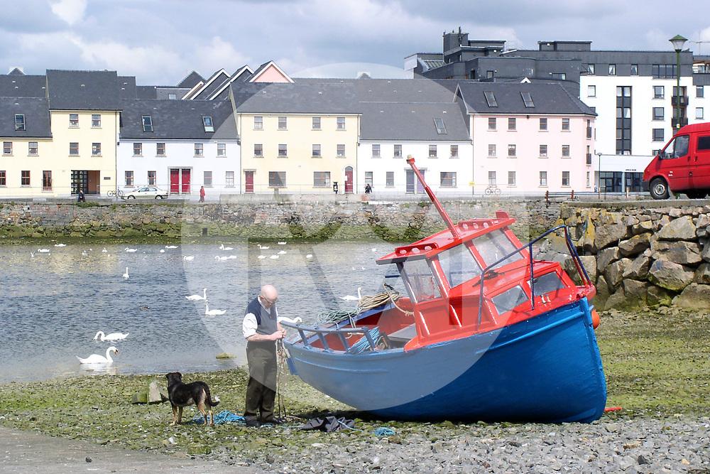 IRLAND - GALWAY - Ein alter Mann mit Hund und Boot, im Hintergrund Häuser am 'The Long Walk' an der Mündung des Corrib - 19. Juli 2004 © Raphael Hünerfauth - http://huenerfauth.ch
