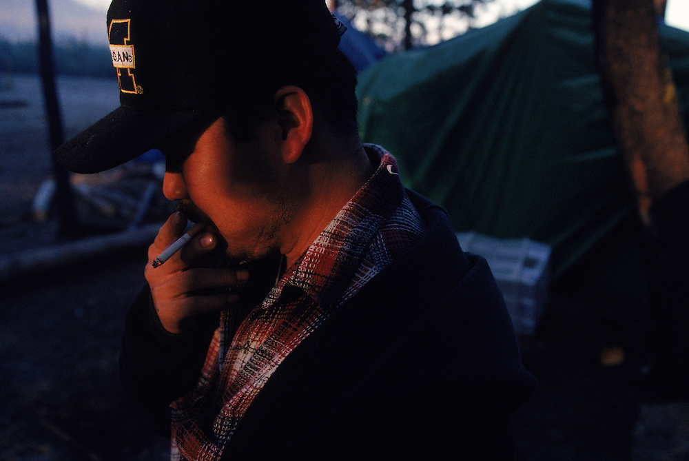 Laotian immigrant Joe Bounehaven smokes a cigarette as the sun rises over the official Mushroom Camp in the Willamette National Forest of Oregon. Matsutake mushrooms are picked during October and November. More than 2,000 pickers participate in the 60-day harvest. Please contact Todd Bigelow directly with your licensing requests.