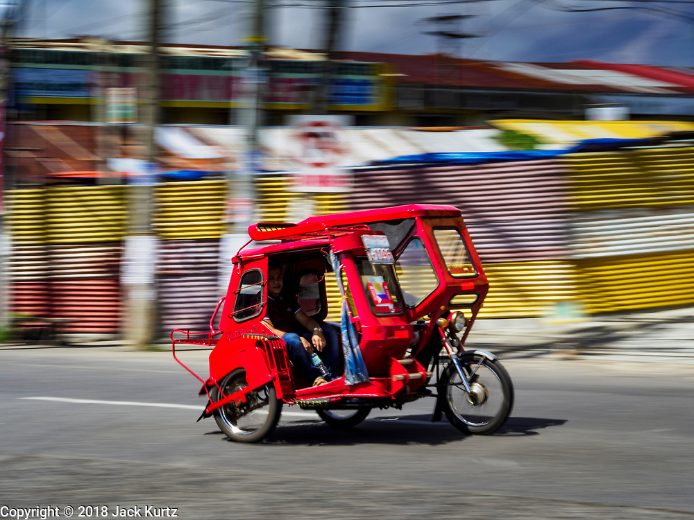 """31 JANUARY 2018 - LEGAZPI, ALBAY, PHILIPPINES: """"Tricycle taxis"""" on the streets of Legazpi, Philippines. Tricycle taxis are motorcycles with sidecars, similar to tuk-tuks and trishaws found in other countries in Asia.        PHOTO BY JACK KURTZ"""
