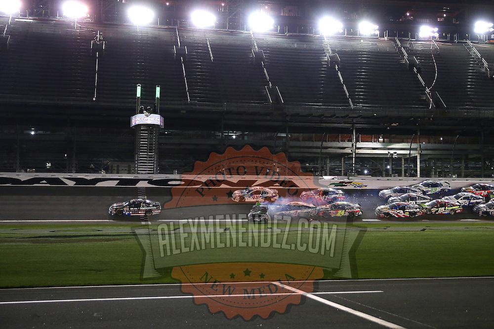 NASCAR Sprint Cup driver Dale Earnhardt Jr. (88) crosses the finish line for the win as Denny Hamlin (11) wrecks during the 57th Annual NASCAR Coke Zero 400 stock car race at Daytona International Speedway on Monday, July 6, 2015 in Daytona Beach, Florida.  (AP Photo/Alex Menendez)