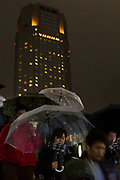 People cross a footbridge holding umbrellas in the rain under the Cerulean Tower in Shibuya, Tokyo, Japan. Friday December 8th 2017