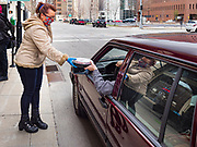 15 APRIL 2020 - DES MOINES, IOWA: CANDICE DEAL hands a free pasta meal to a person in a car at Centro, a restaurant in Des Moines. The owners of Centro handed out 250 pasta meal Wednesday to give back to the hospitality workers in Des Moines. All of the restaurants in Des Moines are closed to sit down service and many that stayed open for take out service have closed as the shutdown has dragged on. Most non-essential businesses in Iowa are closed until 30 April. Because of business closings caused by the Novel Coronavirus (SARS-CoV-2) pandemic, well over 100,000 Iowans filed first time claims for unemployment in the last three weeks, more than applied during the peak of the Great Recession of 2008. Local food banks have seen an unprecedented spike in people seeking nutritional assistance.     PHOTO BY JACK KURTZ