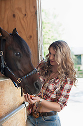 Young woman feeding her brown horse in barn, Bavaria, Germany