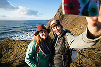 Young women taking a selfie while hiking along the Oregon Coast Trail. Oswald West State Park, OR.