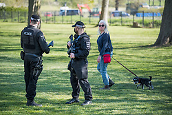 © Licensed to London News Pictures. 17/04/2021. Windsor, UK. A woman walks her dog past armed police on The Long Walk, next to Windsor Castle, in Windsor, Berkshire, ahead of the funeral of Prince Philip, The Duke of York. Prince Philip, the Consort of the longest reigning English monarch in history, Queen Elizabeth II, died on 9 April 2021, two months before his 100th birthday. . Photo credit: Ben Cawthra/LNP