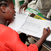 INDIVIDUAL(S) PHOTOGRAPHED: Unknown. LOCATION: Onigbongbo Health Care Center, Lagos, Nigeria. CAPTION: The secretary of the Onigbongbo Health Care Center updates the register that details beneficiaries' appointments, illnesses, treatments, and other health-related matters.