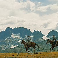 Horseback riders gallop with mountains in the background.