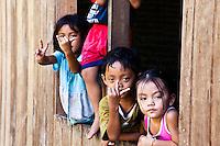 Children playing at a window in Nanga Sumpa Longhouse in Sarawak.