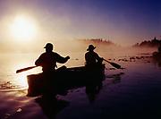 Misty morning sunsrise silhouetting Karen Crosby and Scott Stolnack paddling canoe on Loon Lake near Soldotna, Kenai Peninsula, Alaska.  (MR)