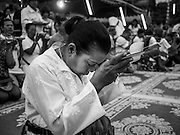"""15 MARCH 2014 - NAKHON CHAI SI, NAKHON PATHOM, THAILAND: A woman prays at the beginning of the Wat Bang Phra tattoo festival. Wat Bang Phra is the best known """"Sak Yant"""" tattoo temple in Thailand. It's located in Nakhon Pathom province, about 40 miles from Bangkok. The tattoos are given with hollow stainless steel needles and are thought to possess magical powers of protection. The tattoos, which are given by Buddhist monks, are popular with soldiers, policeman and gangsters, people who generally live in harm's way. The tattoo must be activated to remain powerful and the annual Wai Khru Ceremony (tattoo festival) at the temple draws thousands of devotees who come to the temple to activate or renew the tattoos. People go into trance like states and then assume the personality of their tattoo, so people with tiger tattoos assume the personality of a tiger, people with monkey tattoos take on the personality of a monkey and so on. In recent years the tattoo festival has become popular with tourists who make the trip to Nakorn Pathom province to see a side of """"exotic"""" Thailand.   PHOTO BY JACK KURTZ"""