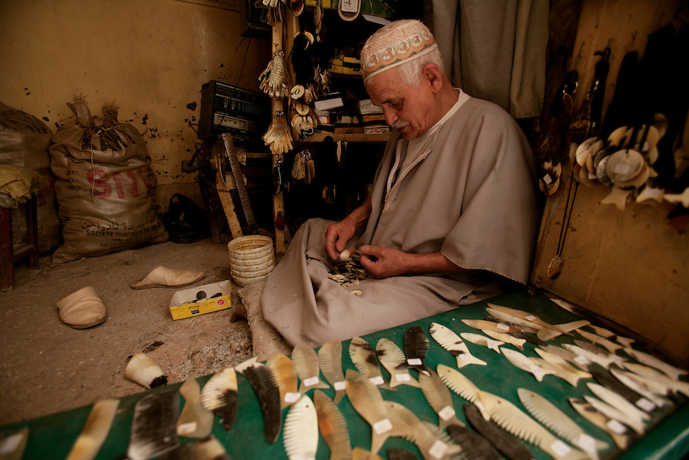 Artisan manufacturing combs from cow horns in a traditional shop.