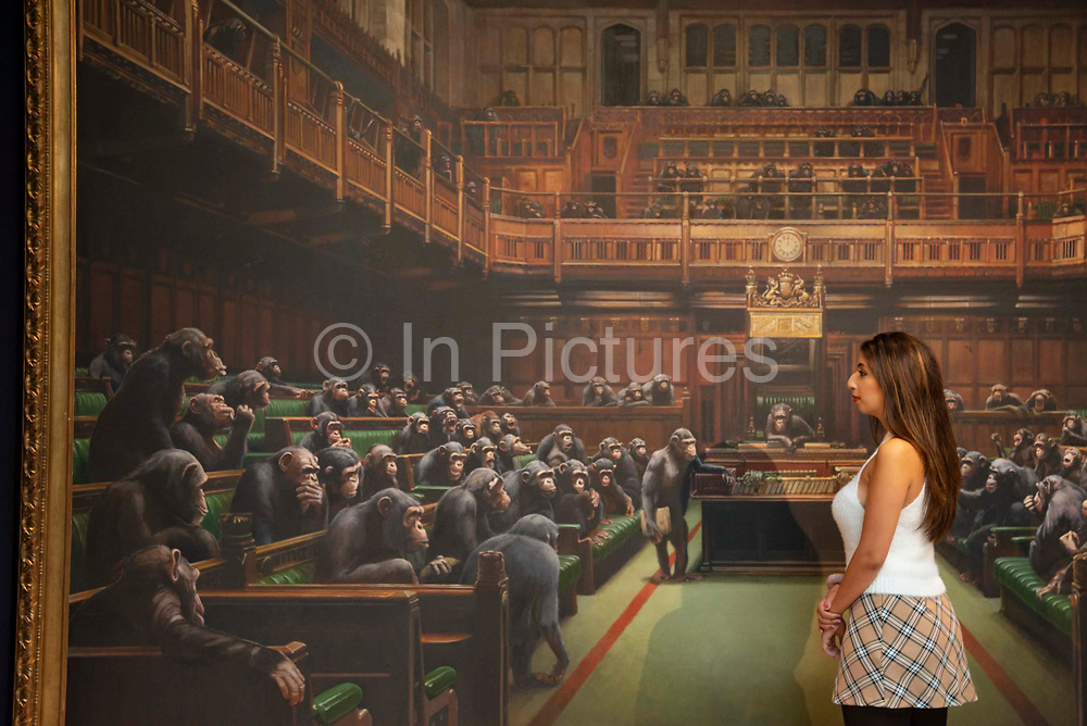 A gallery assistant views  Banksy's Desolved Parliament at Sothebys auction house in London, United Kingdom on 27th September 2019. The work is estimated to reach GBP 1.5 - 2 million when it goes under the hammer.