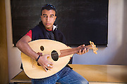 A young man poses with a traditional musical instrument in a classroom in the medieval city of Fes El-Bali, Morocco.