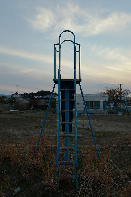 A slide in a n abandoned playground in the town of Tomioka, Futaba District of Fukushima, Japan. Monday April 29th 2013. The town was evacuated on March 12th after the March 11th 2011 earthquake and tsunami cause meltdowns at the nearby Fukushima Daichi nuclear power station. It lies well within the 20 kms exclusion zone though parts of the town have recently been opened again to allow locals to visit their property during daylight hours.