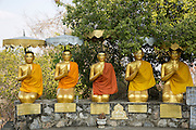 Five golden Buddhist statues covered with traditional orange robes in Vajrasana kneeling meditation position on a wall covered with traditional orange robes in Wat Banan, Battambang region, Cambodia, South East Asia. (photo by Andrew Aitchison / In pictures via Getty Images)