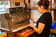 Waitress uses 100 year old cash register, pizza cafe, Puerto Natales, Patagonia, Chile.