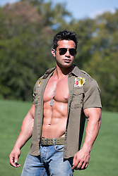 muscular man with an open shirt wearing sunglasses outdoors in Central Park, New York