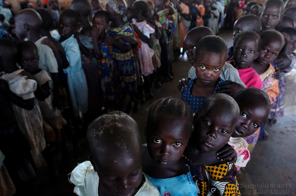 Children in day care at Coope Camp in Gulu District, north Uganda, stand in line before going out to play on October 6, 2006. Coope Camp, with a population of approximately 18,000, is one of 76 camps outside the town of Gulu created for internally displaced people in north Uganda. Since the war began in 1987  over 2 million people have moved from their village homes to camps close to the town of Gulu where they can be protected from the LRA, the Lord's Resistance Army, by the UPDF, the Ugandan People's Defense Force. Over the years the LRA are said to have abducted more than 30,000 children for use as soldiers in their army. The children were often tortured and girls were frequently used as sex slaves. Current peace talks between the Ugandan government and the LRA taking place in Juba, southern Sudan, have the north Ugandan community hoping for an end to the 20 year long war..Photo by Erin Lubin
