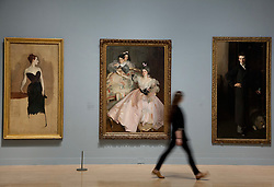 © Licensed to London News Pictures. 30/01/2012. London, UK. Gallery staff walks past artwork by John Singer Sargent  'Study of Mme Gautreau' (left)  'Mrs Carl Meyer and her Children' (Centre) and 'W. Graham Robertson' (Right) at a new Tate Exhibition entitled Migrations: Journeys into British Art. The Exhibition explores how British art has been influenced by migration and includes work by van Dyck, Whistler, Mondrian and Steve McQueen. Photo credit: Matt Cetti-Roberts/LNP