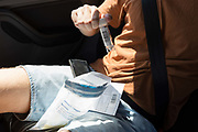 A young man in his twenties pushes a swab up his nose while sitting in the rear seat of a car during a self-administered Coronavirus COVID-19 test in south London. There are four steps to the self-administered Covid-19 test inserting a swab into the nose and throat which the public works through in their car, windows up and all communications with army personnel via phone, in a south London leisure centre, on 2nd June 2020, in London, England. The kit provided consists of a booklet, plastic bag, swab, vial, bar codes and a sealable biohazard bag. The swab sample is taken from the back of the throat and nasal passage with the contents sealed and returned to soldiers through a narrow window. The whole process takes between 5-10mins with results available within 48hrs.