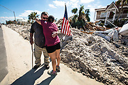 Thomas L Wood hugged by his daughter, Brandy Wood Jessen in front of his hotel, the Driftwood Inn in  Mexico Beach, Florida that was badly damaged by Hurricane Michael.
