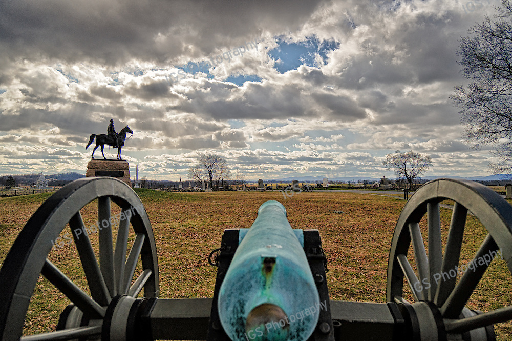 View of the Gettysburg Battlefield from behind one of the many 12 pounder Napoleon Cannons. This Cannon is from the 3rd United States  Artillery Consolidated Batteries F and K . General George G Meade Memorial is to the left. The Cannon is facing in the direction of the Angle, the Confederate High Water Mark and The Copse of Trees