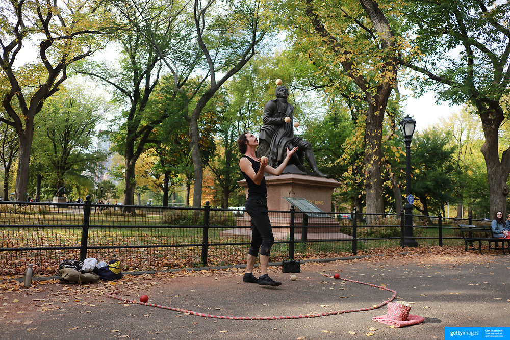 NEW YORK, NEW YORK - NOVEMBER 4: A busker juggling balls in front of the statue of Scottish national poet Robert Burns in a fall scene in Central Park, Manhattan, New York. 4th November 2017. (Photo by Tim Clayton/Corbis via Getty Images)