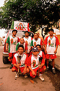 """Male group of pilgrims to the Basilica de Guadelupe, in group on roadside wearing""""Our Lady of Guadelupe shirts."""